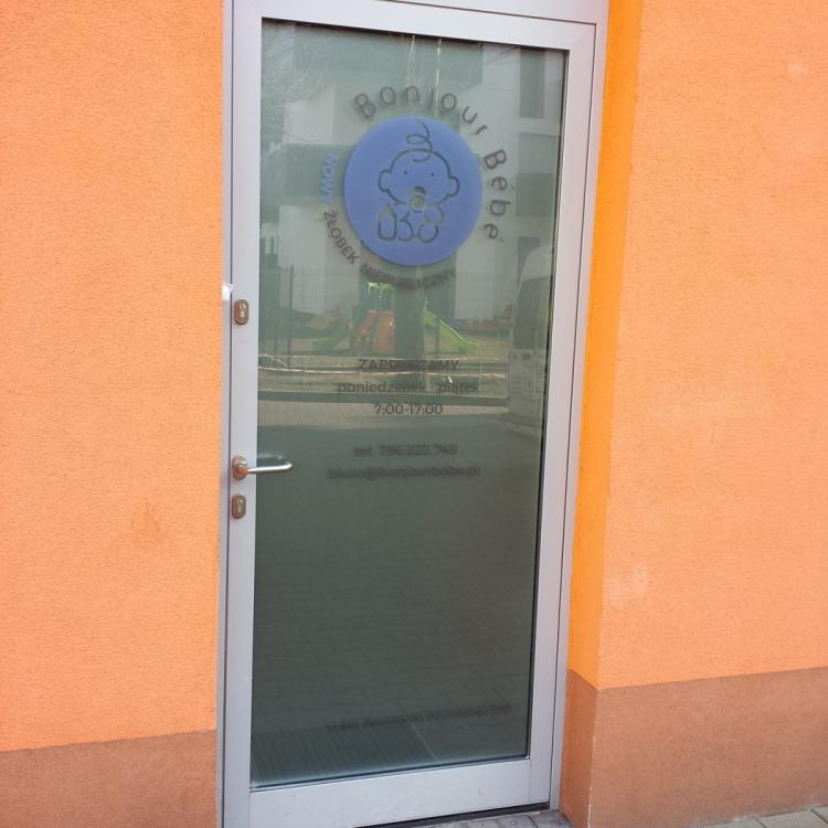 Naklejanie reklamy na drzwi wejściowe